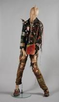 Korte zwart leren jas, kleurig beschilderd en bewerkt met veiligheidsspelden, buttons en tape, punkkleding