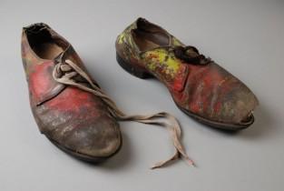 Paar leren heren veterschoenen beschilderd met rode, gele en groene verf en verschillende veters, punkkleding