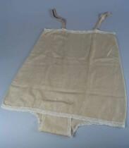Combinaison ofwel hemd van beige zijde met smalle rand crèmekleurig kant als garnering langs borstrand en beenranden