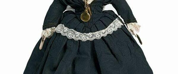 Poppenhuispop, beschilderd porseleinen gezicht met roze teint, houten armen, stoffen lijf en benen, gekleed in zwarte jurk met wit kant en veel lagen ondergoed