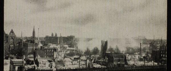 """Foto van vernielde gebouwen en puin, waar heropgebouwde spoorviaduct doorheen loopt, met de tekst """"Omg. Ged. Binnenrotte"""""""