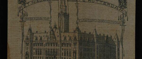Damastweefsel in licht- en donkergrijs linnen met voorstelling van het nieuwe stadhuis te Rotterdam, in ivoorkleurige lijst