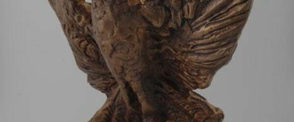 """Opvliegende vogel Feniks op een rechthoekig voetstuk met """"1945 Rotterdam Gloria Fenix 1995"""" en """"Ooms - Makelaars 1925 - 1995"""""""