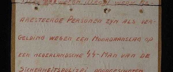 """Kartonnen tekstbordje """"Deze 10 wegen illegal werk gearesteerde Personen zijn als vergelding wegen een Moordaanslag op een nederlandsche SS-Man van de Sicherheitspolizei doodgeschoten."""""""